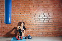 Junge Frau, die nach einem Training in der Turnhalle stillsteht Ein Mädchen sitzt auf einem Hintergrund einer Backsteinmauer in d stockbild