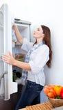 Junge Frau, die nach etwas im Kühlraum sucht Lizenzfreie Stockbilder