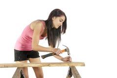 Junge Frau, die Nagel in Holz hämmert Stockfotos