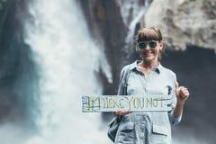 Junge Frau, die nah an Wasserfall auf Bali-Insel aufwirft Lizenzfreie Stockfotografie