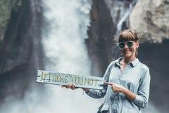 Junge Frau, die nah an Wasserfall auf Bali-Insel aufwirft Stockfotos
