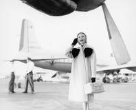 Junge Frau, die nahe bei einem Flugzeug schaut glücklich steht (alle dargestellten Personen sind nicht längeres lebendes und kein Stockfotografie