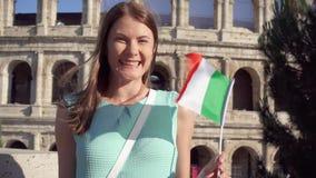 Junge Frau, die nahe Colosseum in Rom, Italien steht Jugendliche, die italienische Flagge in der Zeitlupe wellenartig bewegt stock footage