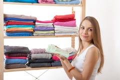 Junge Frau, die nahe der Garderobe steht lizenzfreies stockfoto