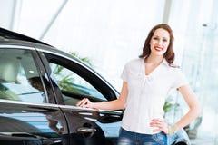 Junge Frau, die nahe einem Auto steht Stockbilder