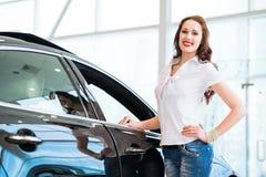 Junge Frau, die nahe einem Auto steht Stockfotografie