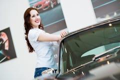 Junge Frau, die nahe einem Auto steht Lizenzfreie Stockfotografie