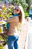 Junge Frau, die nahe einem Blumenzaun steht Stockfotografie
