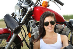 Junge Frau, die nahe einem Motorrad steht lizenzfreie stockbilder