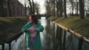 Junge Frau, die nahe einem Palastteilkanal bei einem warmen Frühlingswetter trägt grüne Modejacke - Rothaarigen sich entspannt stock video footage