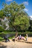 Junge Frau, die nahe einem Sandkasten mit Kindern sitzt Stockfotos