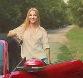 Junge Frau, die nahe einem Sportauto hält Schlüssel steht Lizenzfreie Stockfotografie