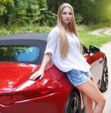 Junge Frau, die nahe einem Sportauto steht Stockbilder