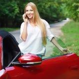 Junge Frau, die nahe einem Sportauto steht und durch beweglichen pH spricht Lizenzfreies Stockbild