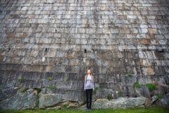Junge Frau, die nahe einer enormen Steinwand steht Architektur Lizenzfreie Stockfotos