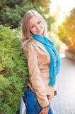 Junge Frau, die nahe einer grünen Hecke steht Stockfoto