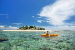 Junge Frau, die nahe Südseeinsel, Mamanuca-Inselgruppe, Fidschi Kayak fährt lizenzfreies stockbild