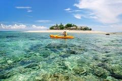 Junge Frau, die nahe S?dseeinsel, Mamanuca-Inselgruppe, Fidschi Kayak f?hrt stockfotos