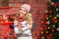 Junge Frau, die nahe schönem Weihnachtsbaum aufwirft Stockfotos