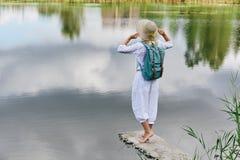 Junge Frau, die nahe See stillsteht Lizenzfreie Stockfotografie