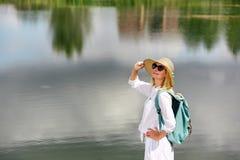 Junge Frau, die nahe See stillsteht Stockbilder