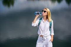 Junge Frau, die nahe See stillsteht Stockfoto