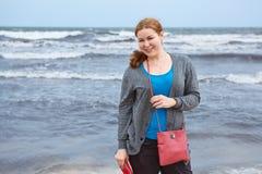 Junge Frau, die nahe stürmischem Meer steht Stockfotos