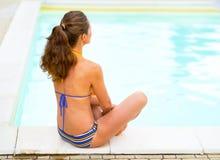 Junge Frau, die nahe Swimmingpool sitzt Hintere Ansicht Stockfoto