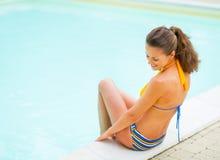 Junge Frau, die nahe Swimmingpool sitzt Hintere Ansicht Lizenzfreie Stockfotografie