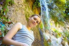 Junge Frau, die nahen Wasserfall steht Lizenzfreie Stockfotografie