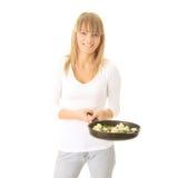 Junge Frau, die Nahrung kocht Stockfotografie