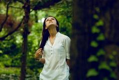 Junge Frau, die Natur im Sommergarten genießt Stockbilder