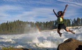 Junge Frau, die in Natur springt Stockfotografie