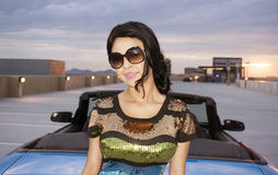 Junge Frau, die neben konvertierbarem Auto steht Stockfoto