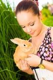 Junge Frau, die nettes Kaninchen lächelt und hält Lizenzfreie Stockfotografie