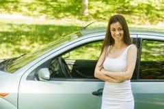 Junge Frau, die Neuwagen zeigt stockbilder