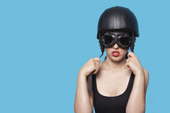 Junge Frau, die nostalgischen Sturzhelm und Schutzbrillen gegen blauen Hintergrund trägt Lizenzfreie Stockbilder
