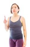 Junge Frau, die oben ihren Finger zeigt Stockbilder