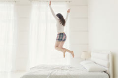 Junge Frau, die oben mit den Händen oben angehoben springt Stockbild