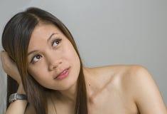 Junge Frau, die oben schaut Stockbild