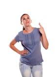 Junge Frau, die oben schaut und ihre Finger kreuzt Stockfotografie