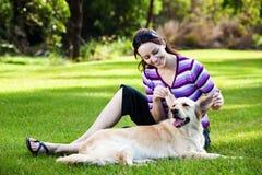Junge Frau, die Ohren des goldenen Apportierhunds zieht Stockfoto