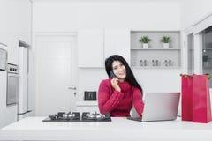 Junge Frau, die online in der Küche kauft stockbilder