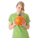 Junge Frau, die orange Kürbis anhält Stockfotos