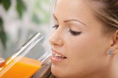 Junge Frau, die Orangensaft trinkt Lizenzfreie Stockfotos