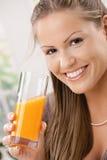 Junge Frau, die Orangensaft trinkt Lizenzfreies Stockbild