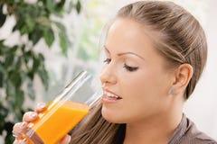 Junge Frau, die Orangensaft trinkt Lizenzfreies Stockfoto