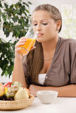 Junge Frau, die Orangensaft trinkt Lizenzfreie Stockbilder