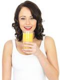 Junge Frau, die Orangensaft trinkt stockbild
