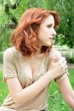Junge Frau, die am Park sitzt Stockfoto